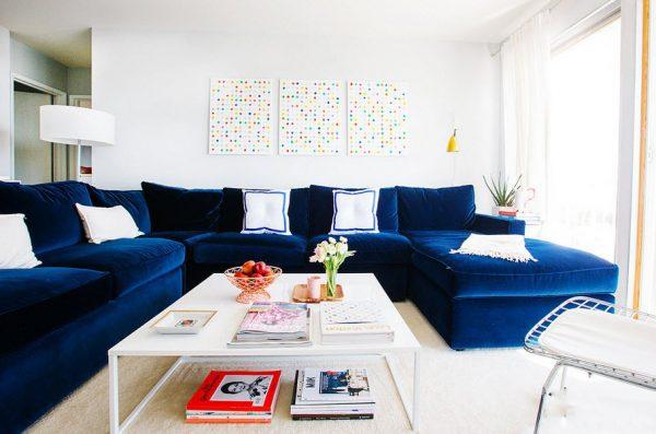 Большой синий диван в интерьере светлой гостиной