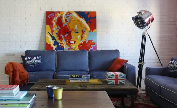 Стильный интерьер гостиной с синим диваном