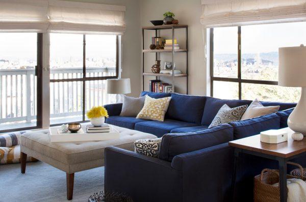 Дизайн гостиной с синим диваном.