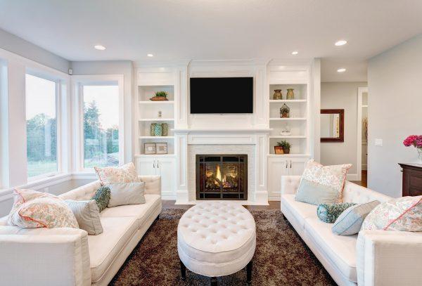 Уютная белая гостиная с камином в загородном доме